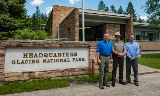 Secretary Zinke wears a blue polo and khaki pants and stands in front of a brick building next to a sign for Glacier National Park with two other men, one of them in an NPS uniform.