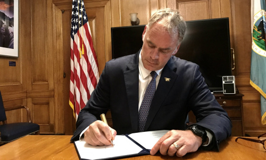 Secretary Zinke, a white man with gray hair wearing a suit and tie, sits at a small table in a wood paneled office signing a piece of paper in a folder.