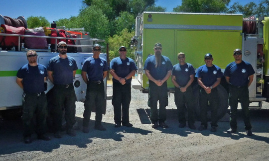 A fire crew, dressed in blue uniform t-shirts, poses in front of its vehicles.