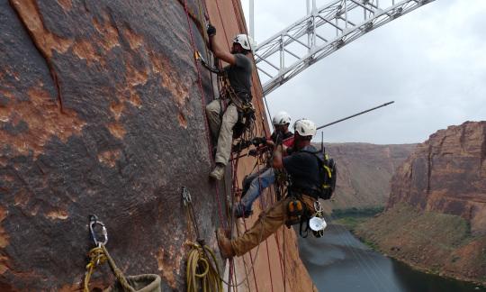 BOR employees inspecting a rock wall beside a dam