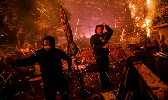 Two men with hoses, surrounded by fire and sparks.