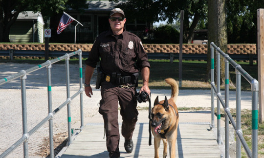 Federal Canine Officer walks with dog