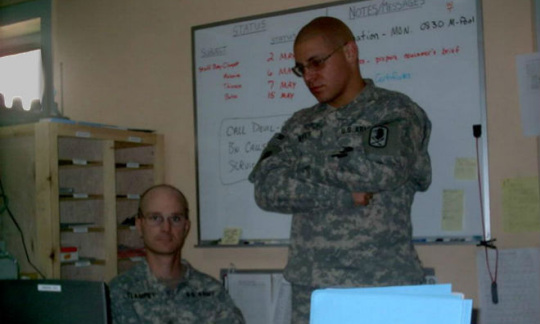 Two men in camouflage uniforms in an office.