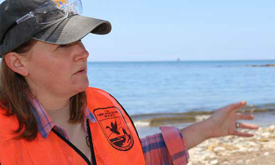 A woman in an orange vest gestures towards the ocean.