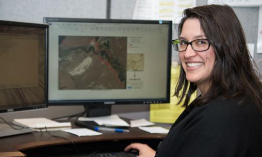 A woman at a computer desk, facing camera.