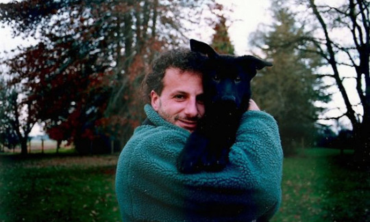 Rich Guadagno stands in a grassy field by the woods holding a cute, black dog.