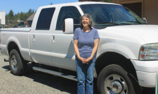 Rita Poe stands in front of her white truck