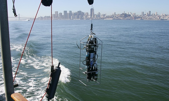 Instruments used to measure a variety of water quality constituents are deployed off the research vessel's boom, with the San Francisco skyline in the background. Photo credit: USGS