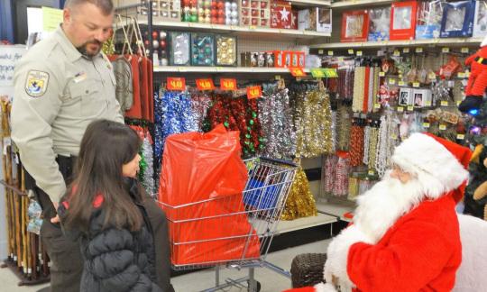 Man in uniform takes kids to meet Santa (seated)