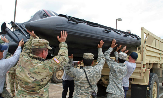 Texas Army National Guardsmen join members of a Texas Task Force One Swift Water Rescue Team.