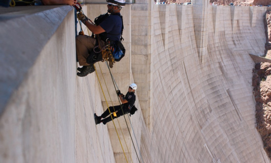 Two people use ropes to rappel down the concrete face of the Hoover Dam.
