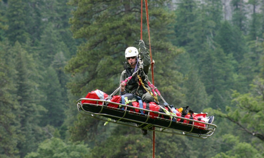 A female park ranger and a rescue stretcher are suspended under a helicopter by a rope.