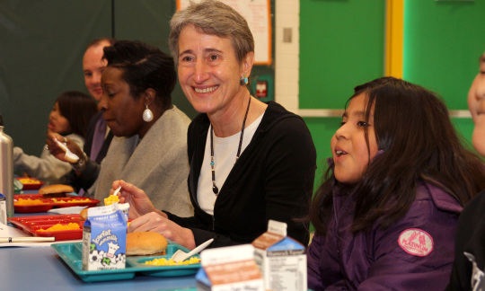 Secretary Jewell sitting at a school lunch table eating and smiling with Native American students.