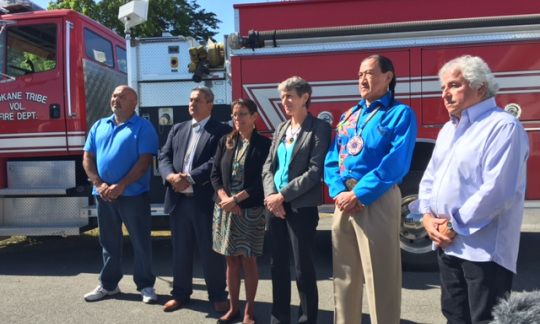 Secretary Jewell stands in front of a red fire truck with five members of the Spokane Tribe of Indians Business Council