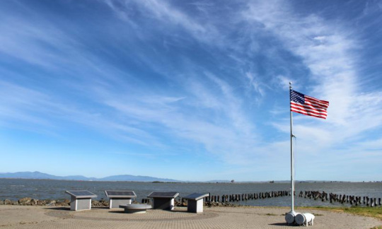 The American flag billows in the wind at Port Chicago.