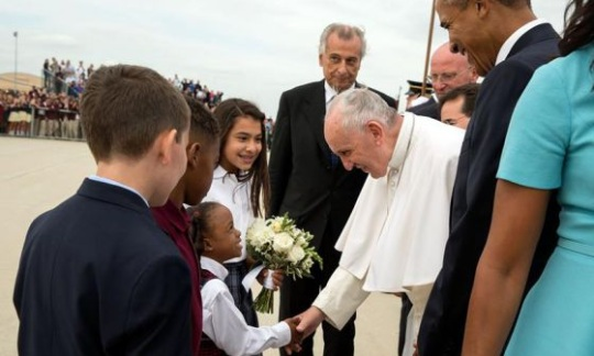 His Holiness Pope Francis hands flowers to a young girl