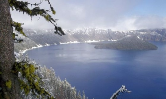 Crater Lake National Park shows a dusting of snow around the edges