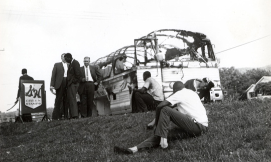 Historic image of 1963 firebombing of a freedom riders bus burning on the side of a highway.