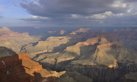 The setting sun casts light and shadow over the majestic spread of the Grand Canyon.