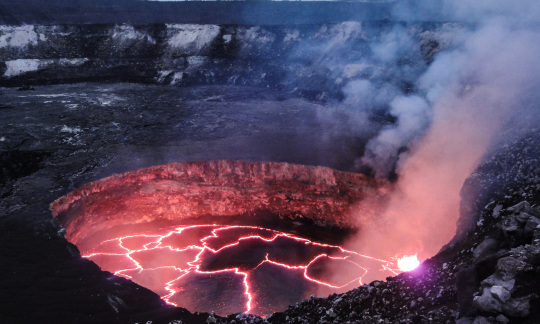 A red hot pool of lava bubbles at the bottom of a large, round hole in the burnt earth.