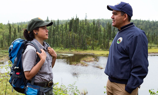 Deputy Secretary Mike Connor speaks with a young woman wearing a backpack near a lake surrounded by trees.