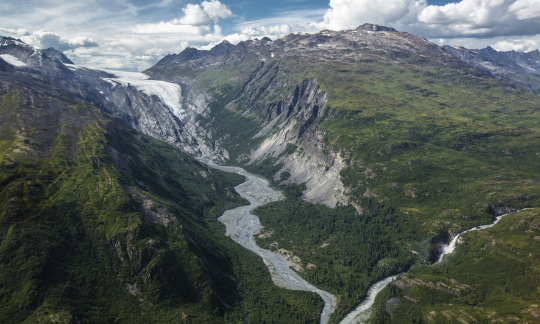 A river streams from a glacier between two mountains in an epic Alaska landscape.