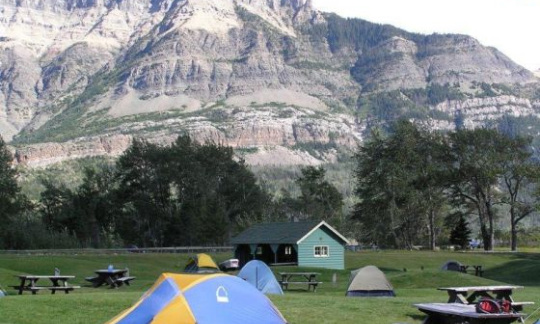 Tents below mountains at Camping at Waterton-Glacier International Peace Park in Montana