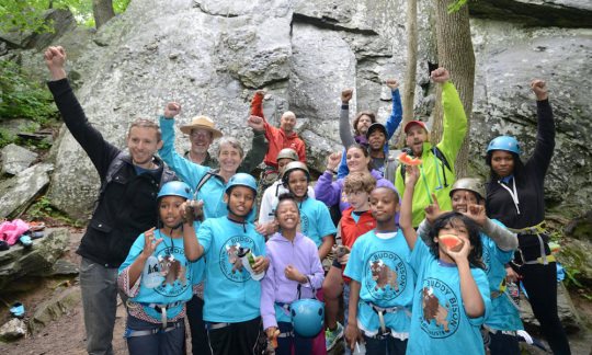 Secretary Jewell standing and cheering with children in the woods.