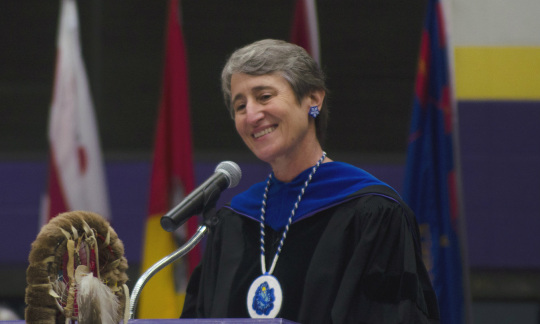 Secretary Jewell dressed in a graduation gown and speaking at a podium.