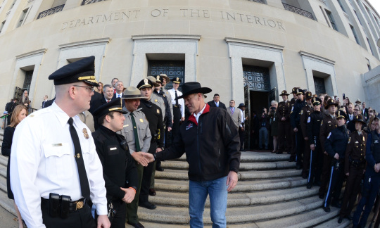 Secretary Ryan Zinke wears a cowboy hat and shakes hands with a large group of Interior employees on the steps of the Interior building.