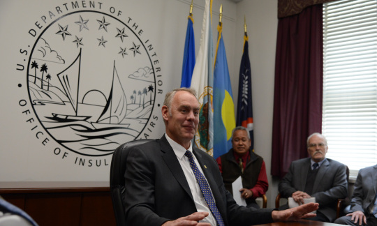 Secretary Ryan Zinke sits at a table wearing a suit and talking to a group of employees in a conference room with flags in the corner and a circular logo on the wall.