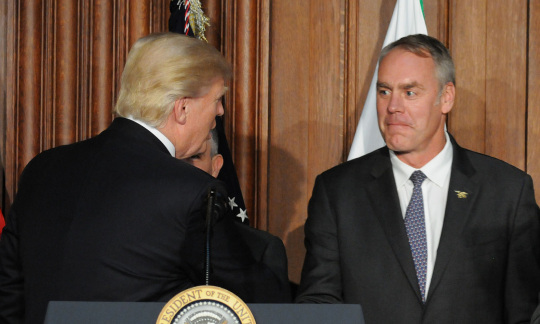 Secretary Zinke shaking hands with President Trump behind a podium in an auditorium.