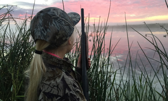 A young girl with blonde hair wears hunting camouflage and holds a shotgun while standing in tall grass and looking at a pink sunrise.