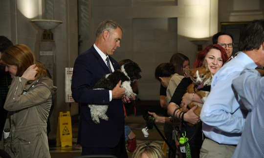Secretary Zinke holds his small dog in his arms surrounded by other men and women