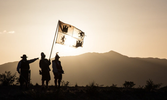 Three men dressed as Spanish explorers wave a flag while standing on a hillside in bright sunlight.