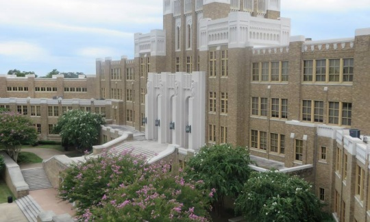 A view of the front of Little Rock Central High School, a large brick building.