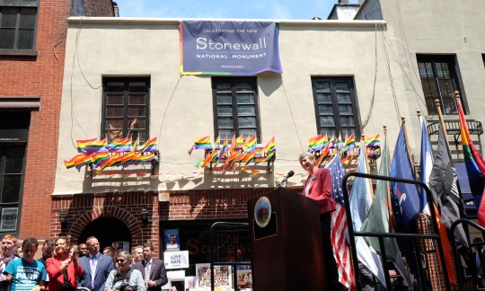 Secretary Jewell stands at a podium and speaks in front of the brick front of Stonewall National Monument.