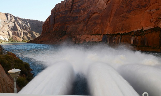 Water rushes through a dam into a river that snakes through canyon cliffs.