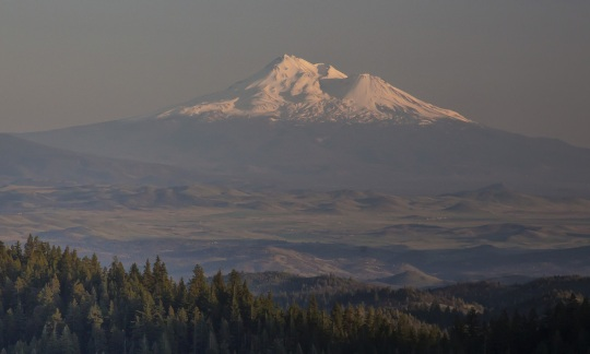 A lone, snow-topped mountain lit by the setting sun stands against a dark sky.