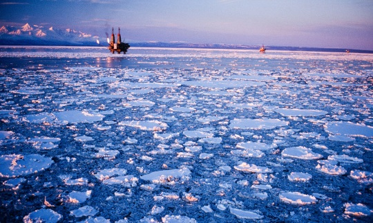 An oil rig sits on the water surrounded by a sheet of broken ice.