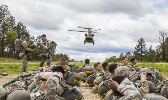 A helicopter lands near a group of paratroopers.