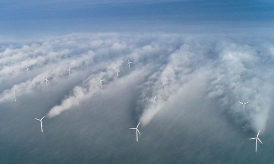 A row of wind turbines stand in the ocean.