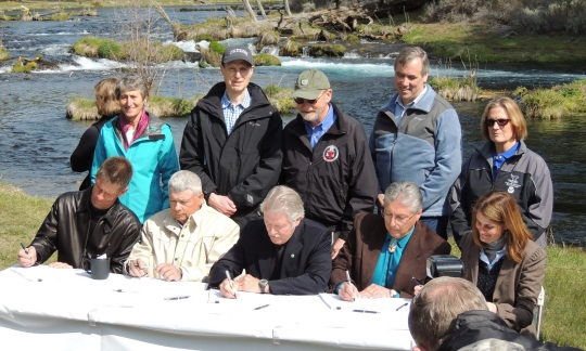Officials gather to sign the agreement by the Klamath River