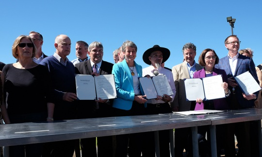 Secretary Jewell and other federal, state and tribal officials standing behind a table and holding up the signed agreement.