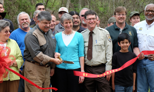 Secretary Jewell and other people smiling and cutting the ribbon to open a new boardwalk.