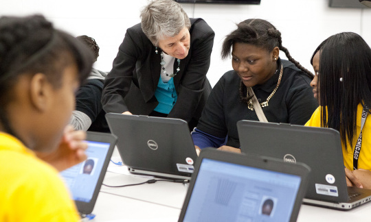 Secretary Jewell and a group of African American students looking at computers in a classroom