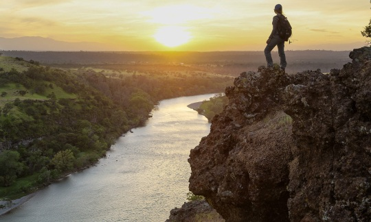 A hiker stands on a bolder overlooking river valley as the sun sets. Photo of Sacramento River Bend Outstanding Natural Area by Bob Wick, BLM.