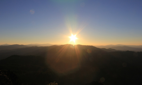 A bright sunset on a clear evening over the hills of Soda Mountain Wilderness in California.