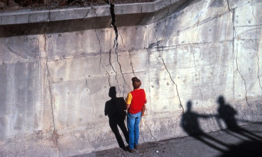 Workers inspect damage to a concrete wall after a 1989 California earthquake