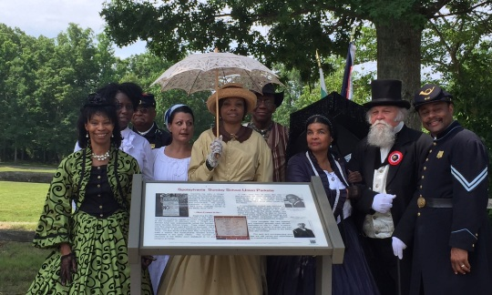A diverse group of people dressed in civil war era clothes and uniforms stand outside near an information sign.